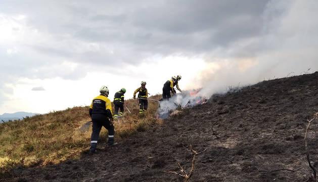 Bomberos trabajan en una quema de pastos de montaña.