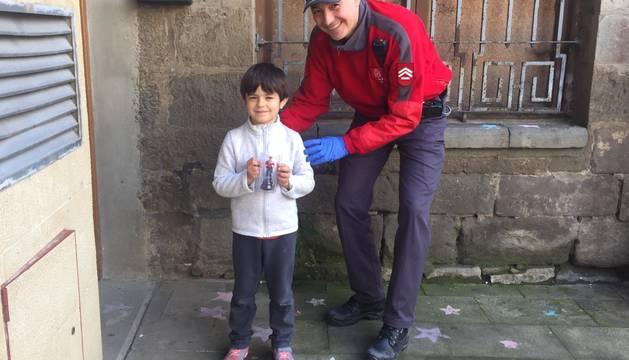 Imagen de Javier junto a un agente de Policía Foral, que acudió a su domicilio para hacerle entrega de un regalo por su diente.