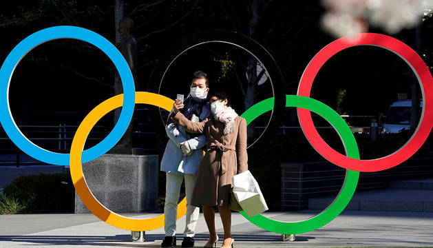 Una pareja con máscaras protectoras se toma selfies de un monumento de los Anillos Olímpicos frente a la sede del Comité Olímpico de Japón en Tokio.