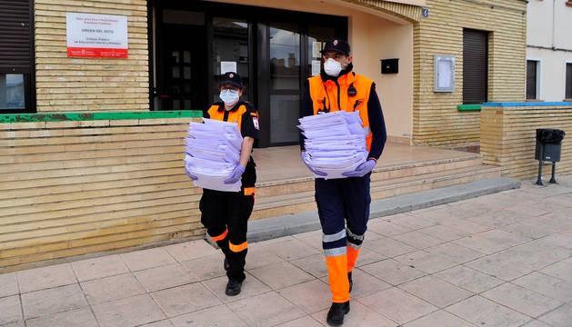 foto de Joana Cajidor (izda.) y Osama Ihdi salen del colegio de Caparroso con las tareas para los alumnos.
