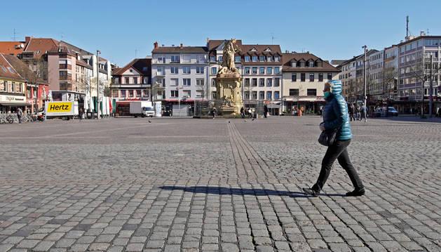 Foto de una mujer paseando por una plaza vacía en Mannheim, Alemania.