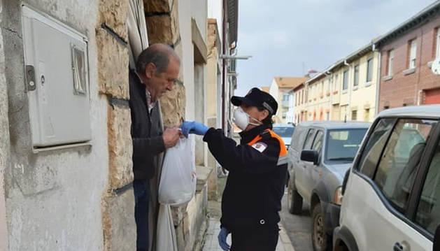 Fotos de un voluntario de Protección Civil llevando comida y medicamentos a un vecino.