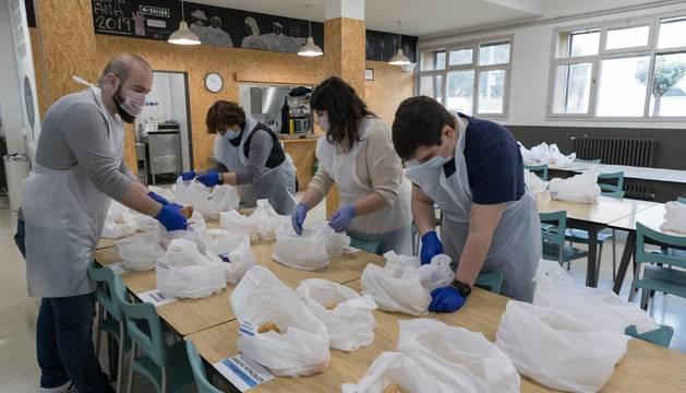 Un grupo de voluntarios y trabajadores de Villa Javier prepara los taper para entregar a los usuarios.