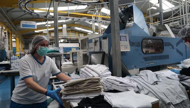 Foto de trabajadora, ordenando este jueves uniformes limpios de sanitarios en la planta de Noáin de Ilunion-Lavanor.