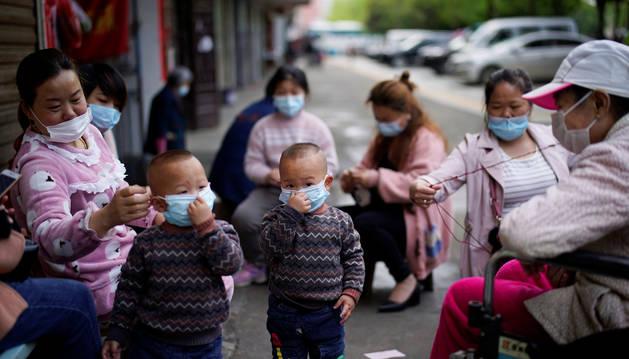 Foto de Mujeres y niños con mascarillas en Xianning.