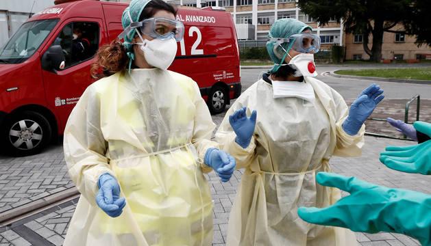 Dos enfermeras que acaban de trasladar en ambulancia a un enfermo que ha dado positivo en el test del COVID-19.