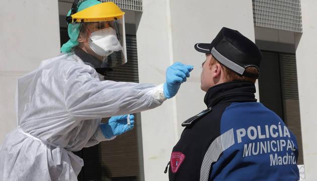 Una sanitaria realiza un test a un policía municipal de Madrid.
