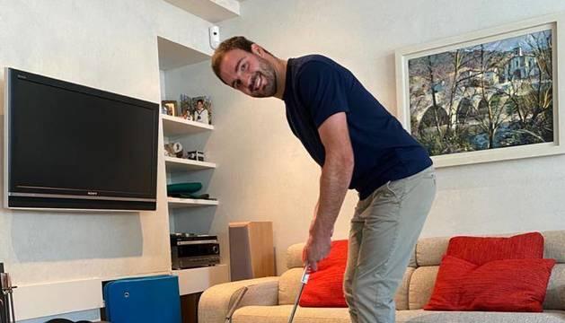 David Borda, ayer por la mañana, tirando un putt en la alfombra que ha colocado en su salón.