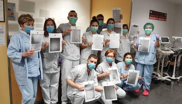 Un grupo de los sanitarios que trabajan en la sexta planta del antiguo Hospital Virgen del Camino, donde hay ingresados positivos, con algunas de la cartas recibidas por anónimos.