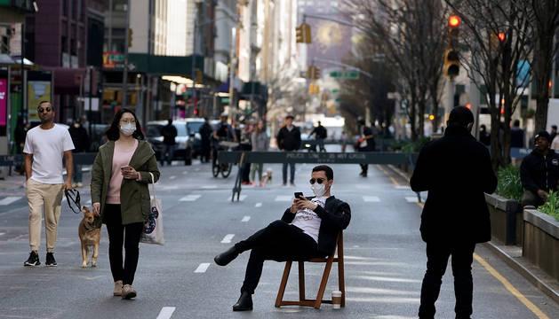 Un hombre, sentado en una silla en plena Park Avenue de Nueva York, cerrada al tráfico debido al coronavirus.