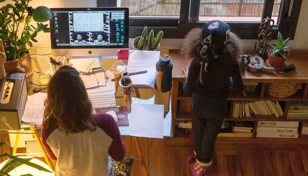 foto de Una mujer realiza teletrabajo en su casa mientras su hija juega a su lado