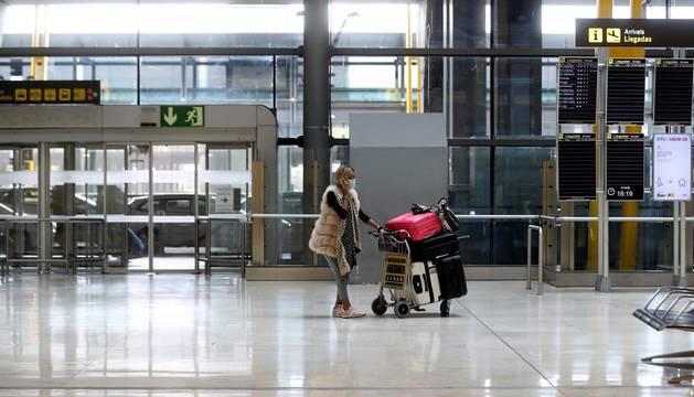 Foto de una mujer en la terminal 4 del aeropuerto Adolfo Suárez Madrid Barajas durante la crisis del coronavirus.