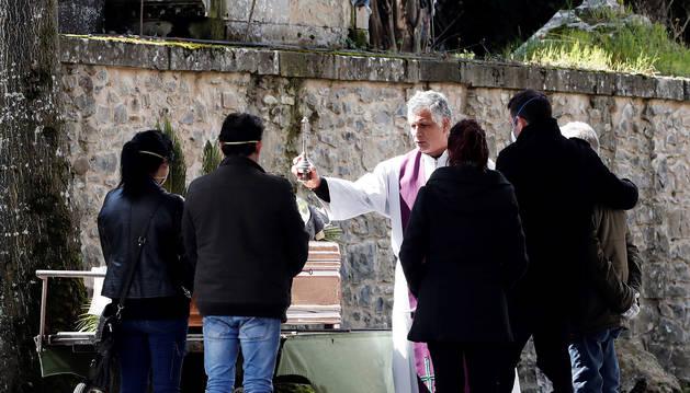 El sacerdote reza un responso antes del traslado del féretro al interior del cementerio, donde sólo pueden estar presentes tres personas.