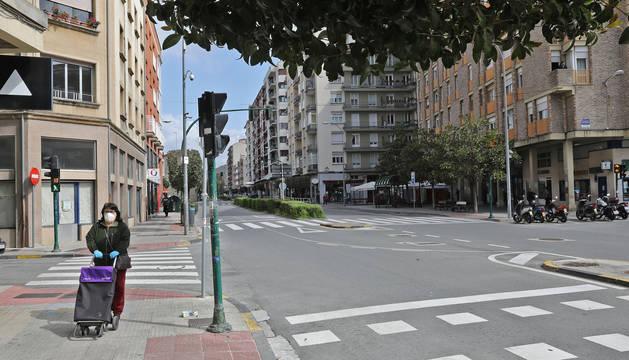 Una mujer con el carro de la compra y en solitario por la anteriormente concurrida calle Mayor de Burlada.