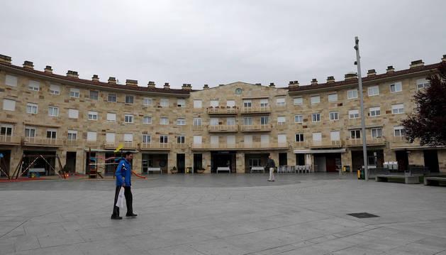 Foto de dos personas atravesando la plaza Mutiloa de Mutilva durante la pandemia de coronavirus.