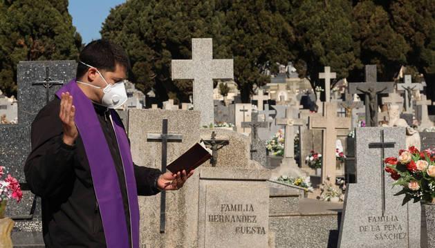 Foto de un sacerdote rezando un responso en un cementerio durante la pandemia de coronavirus.