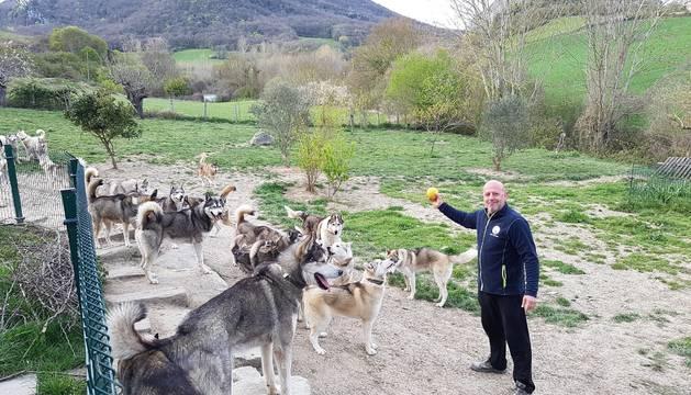 Baltasar Gallardo, junto a algunos de los perros con los que convive y compite en carreras de trineos, en el terreno de su casa