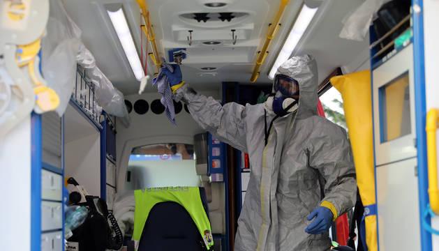 Un voluntario de bomberos desinfecta una ambulancia en el CHN.