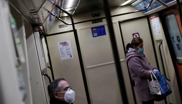 Dos pasajeros del metro de Madrid se cubren con máscarillas.