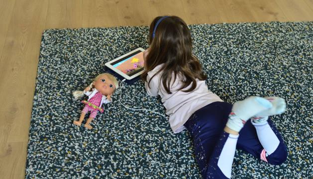 Una niña lee en el salón de su casa.