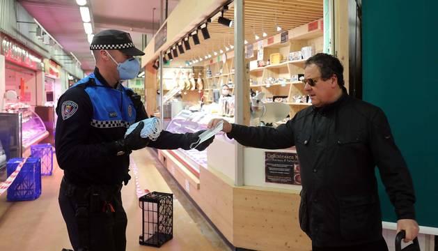 Agentes reparten mascarillas para prevenir el coronavirus en Pamplona.
