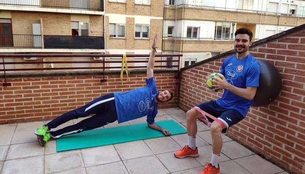Los jugadores del Aspil Sergio González -a la izda.- y Ferran Plana realizan varios ejercicios físicos en la terraza de su casa en Tudela.