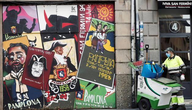 Un trabajador del Ayuntamiento de Pamplona desinfecta un portal del Casco Viejo junto a unos carteles alusivos a los Sanfermines en una jornada donde millones de españoles afrontan otro día mas de confinamiento debido a la crisis del coronavirus.