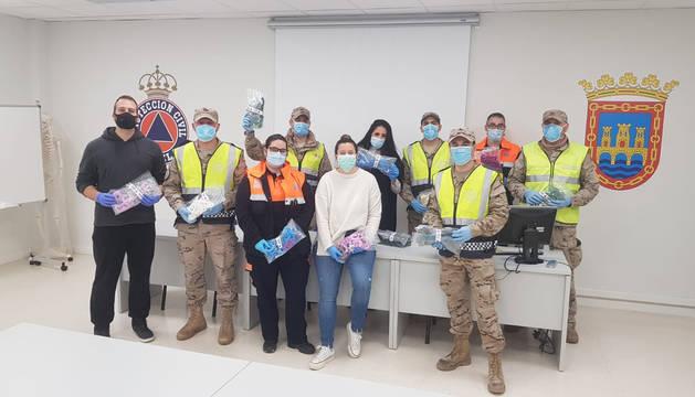 Representantes del Ayuntamiento, militares de Bardenas, voluntarios de Protección Civil, con los ganchos.