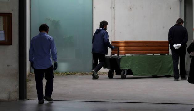 foto de Operarios del cementerio de Pamplona trasladan un féretro el pasado sábado por la mañana.
