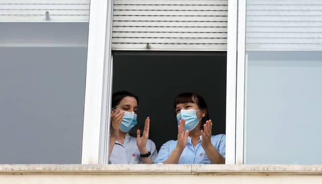 Dos enfermeras aplauden desde una ventana del CHN cubiertas con sendas mascarillas.