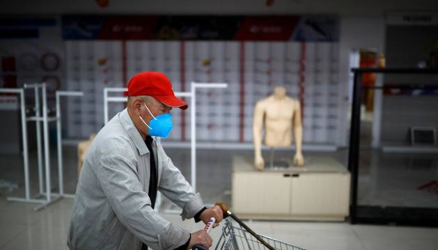 Un hombre empuja un carrito de la compra en Beijing.