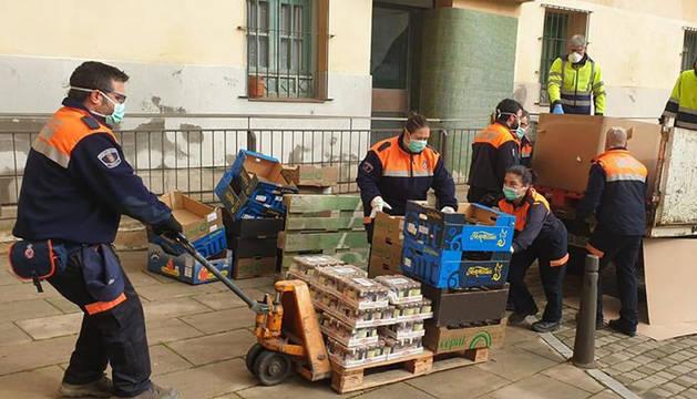 Foto de un grupo de voluntarios de Protección Civil de Tudela descargando alimentos donados para su posterior distribución en la capital ribera durante la pandemia de coronavirus.