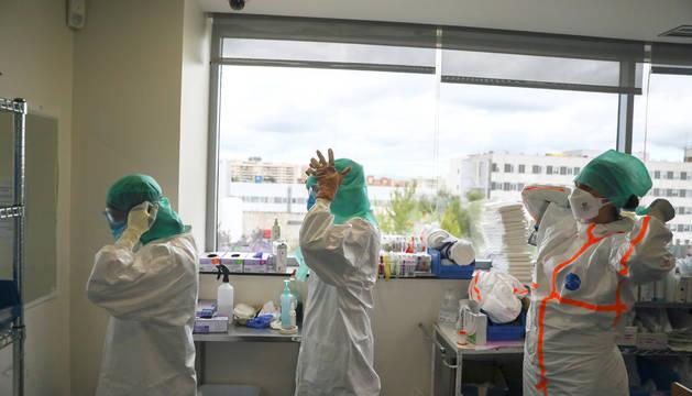 Profesionales médicos se preparan antes de entrar a la UCI en el Hospital de La Paz de Madrid.