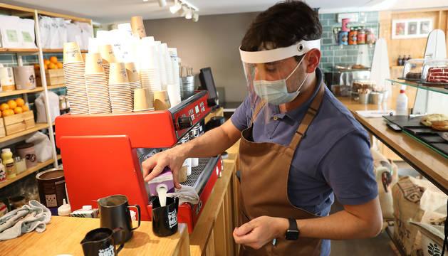 Manuel Spucches, con pantalla y mascarilla, sirve un café.