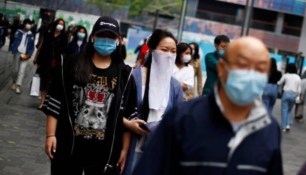 Varias personas caminan por una calle de Pekín cubiertas con mascarillas.