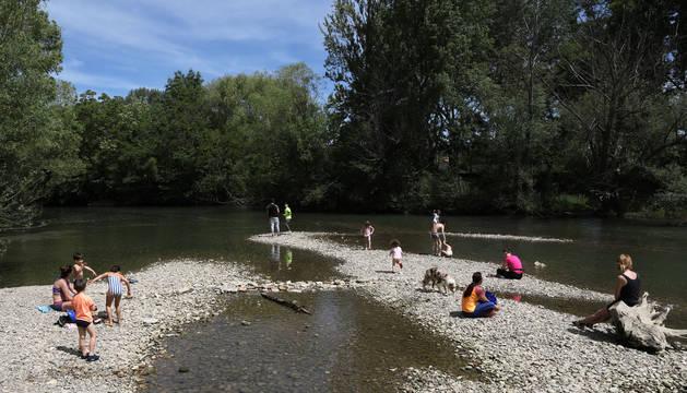 Disfrutar del sol e incluso refrescarse a la orilla del río Arga alivió del calor a decenas de personas.