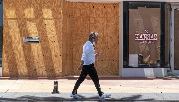 Un hombre con una mascarilla pasea ante un comercio cerrado de la calle Ocean Drive de Miami Beach.