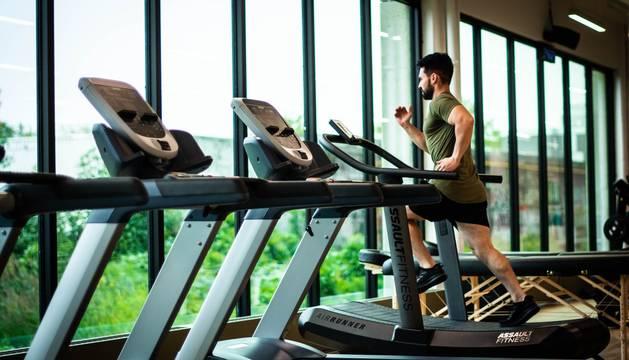 Un hombre se ejercita sobre una cinta en el gimnasio