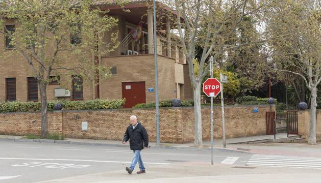 Un hombre camina con el edificio de Servicios Sociales de Tudela a sus espaldas.