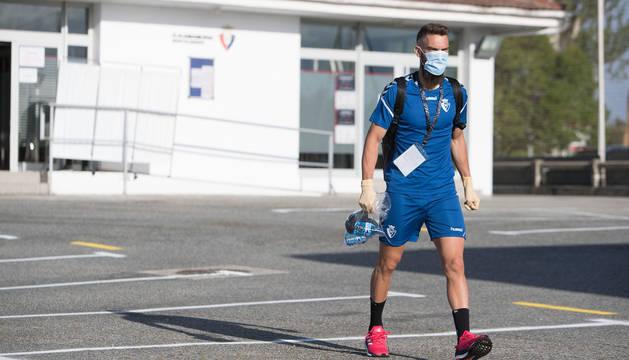 Roberto Torres se dirige al campo de hierba artificial después de haber sido sometido al control de temperatura y peso, ayer en el parking de Tajonar.