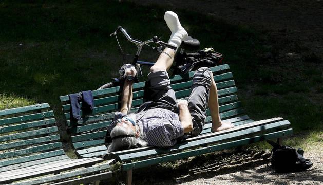 Un ciclista descansa tumbado al sol y cubierto con una mascarilla en el parque Montanelli de Milán.