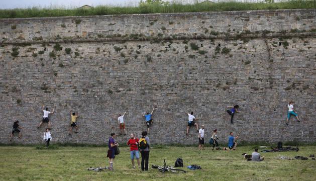 Un grupo de escaladores practica el búlder o escalada horizontal en el 'Muro Largo' -un tramo de 120 metros de la muralla- de la Ciudadela de Pamplona.