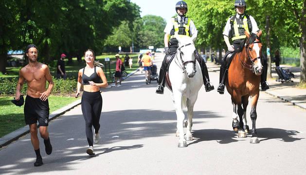 Dos corredores pasan junto a dos policías en el parque Victoria de Londres.