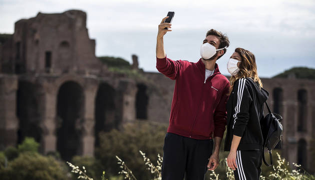 Una pareja cubierta con mascarillas se hace una foto con el Circo Massimo de Roma al fondo.