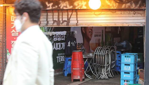 Un hombre pasa por delante de un bar cerrado en Seúl.