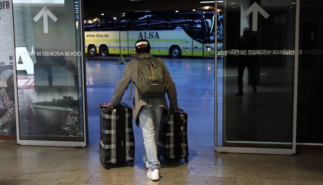 Un hombre se dirige con dos maletas a coger un autobús en la estación de Pamplona.