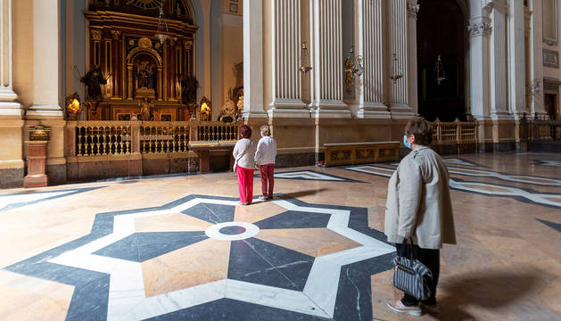 Dos fieles rezan mientras una señora espera su turno en el interior de la basília de El Pilar, este lunes 11 de mayo.