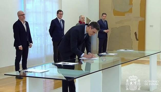 Captura de la señal institucional de Moncloa que muestra al presidente del Gobierno Pedro Sánchez durante la firma, este lunes, con los líderes de las patronales CEOE y Cepyme y de los sindicatos UGT y CC OO.