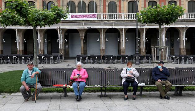El clima desapacible de ayer no impidió que los vecinos de Pamplona disfrutaran de la calle. En la foto, en un banco de la plaza del Castillo.