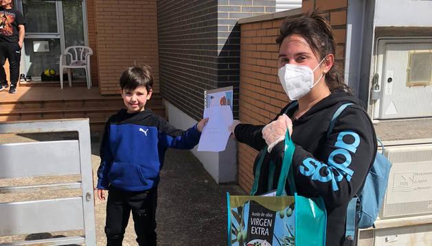 Una voluntaria entrega el diploma y mascarillas a un niño.